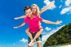 Young beautiful couple having fun on a tropical beach. Stock Photos