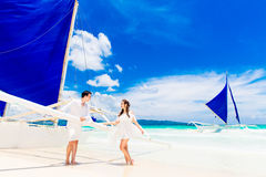 Young beautiful couple having fun on a tropical beach . Tropache Stock Images