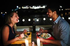 Young beautiful couple having romantic dinner on rooftop. Young beautiful couple in love having romantic dinner at night on rooftop Royalty Free Stock Image