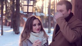 Young beautiful couple hipsters drinking hot tea in winter outdoors. Winter couple smiling happy in Valentine`s day. Beautiful young couple at backyard of their stock footage