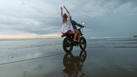 Young beautiful couple hipsters riding retro motorcycle on the beach, outdoor portrait, riding guy and girl, travel