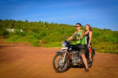 Young beautiful couple hipsters in stylish clothing on the motorcycle posing against a blue sky and green grass. Adventure and. Vacations concept royalty free stock images