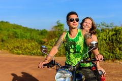 Young beautiful couple hipsters in stylish clothing on the motorcycle posing against a blue sky and green grass. Adventure and stock images