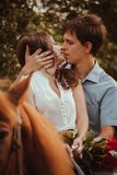 Young beautiful couple  with a horse. Filtered. Selective focus. Royalty Free Stock Image