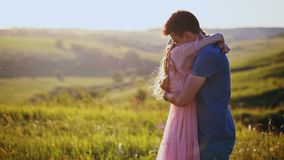 A young beautiful couple hug and kiss, nature, field at sunset. stock video footage