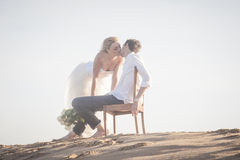 Young beautiful couple kissing at the beach. Young beautiful couple kissing and hanging out together at the beach Royalty Free Stock Photos