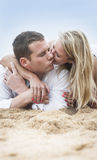 Young beautiful couple kissing on beach sand. Outdoors in the morning Royalty Free Stock Photo