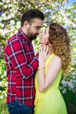 Young beautiful couple kissing in blooming garden. Young beautiful couple kissing in blooming summer garden Stock Photos
