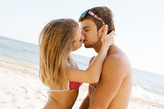 Young beautiful couple kissing at the seaside. Young beautiful couple kissing at the sea shore Royalty Free Stock Image