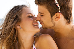 Young beautiful couple kissing on the seaside. Young beautiful couple kissing at the sea shore Stock Image