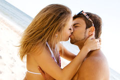 Young beautiful couple kissing on the seaside. Young beautiful couple kissing at the sea shore Stock Photography