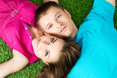 Young beautiful couple laying down together on grass in park Stock Photo