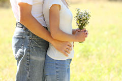 Young beautiful couple in love with a bouquet of flowers in natu Royalty Free Stock Photography