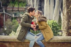 Young beautiful  couple in love celebrating Valentines day presents and toast. Couple in love kissing on street celebrating Valentines day with girl receiving Stock Image