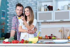 Young and beautiful couple in love is cooking food on the kitchen Stock Photos