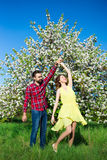 Young beautiful couple in love dancing in blooming garden Stock Photos