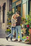 Young beautiful  couple in love kissing on street celebrating Valentines day with rose gift Stock Photos