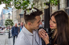 Young beautiful couple in love looking at each other in the eye near the post with flowers while walking in Lviv when filming love Royalty Free Stock Photography