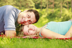 Young beautiful couple in love lying on the grass Royalty Free Stock Images