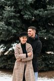 Young beautiful couple in love posig on the street. Young beautiful smiling couple in love posig on the street in winter, having fun together royalty free stock photo