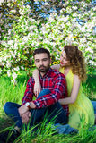 Young beautiful couple in love sitting in blooming garden Stock Photos