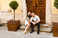 Young beautiful couple in love sitting on old city street. Summer Europe vacation royalty free stock photos