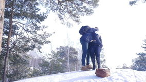 Young and beautiful couple in love walking in the winter woods. They kiss and hug. The girl red scarf stock video