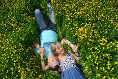Young beautiful couple lying on the grass. Up view. Portrait of a happy young couple lying on fresh green grass with yellow flowers in the park or meadow Royalty Free Stock Photography