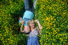 Young beautiful couple lying on the grass. Up view. Portrait of a happy young couple lying on fresh green grass with yellow flowers in the park or meadow Stock Photo