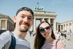 Young couple making selfie against the background of the Brandenburg Gate in Berlin. Young beautiful couple making selfie against the background of the stock photo