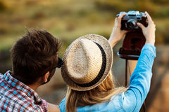 Young beautiful couple making selfie on old camera, canyon background. Stock Image