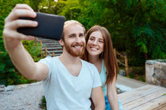 Young beautiful couple making selfie, smiling, walking in park. Outdoor background. Stock Photos