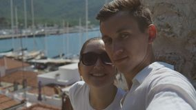 People on holiday in warm countries. Young beautiful couple - man and woman smiling and doing selfie on the background of beautiful view of the sea and boats stock video