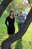 Young beautiful couple in park. Beautiful young couple in park by tree Stock Photos