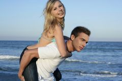 Young beautiful couple playing on the beach. Young beautiful couple playing on the blue beach Royalty Free Stock Images