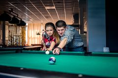 beautiful couple playing billiard together stock images