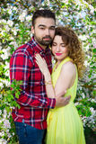 Young beautiful couple posing in blooming garden Royalty Free Stock Photo