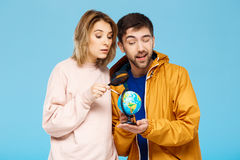 Young beautiful couple posing over blue background. Man wearing rain coat holding small globe. Girl looking through Stock Photos