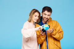 Young beautiful couple posing over blue background. Man wearing rain coat holding small globe. Girl looking through Stock Images