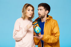 Young beautiful couple posing over blue background. Man wearing rain coat holding small globe. Girl with magnifier Royalty Free Stock Photos