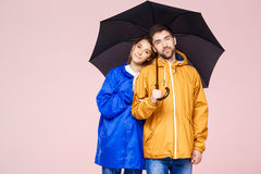 Young beautiful couple posing in rain coats holding umbrella over light pink background. Royalty Free Stock Photo
