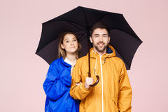 Young beautiful couple posing in rain coats holding umbrella over light pink background. Stock Photography