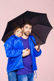 Young beautiful couple posing wearing one rain coat holding umbrella over light pink background. Royalty Free Stock Image