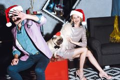 Couple with pug in santa hat Royalty Free Stock Images