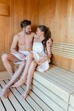 Young and beautiful couple relaxing and hugging in a sauna with Stock Photography