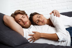 Young beautiful couple relaxing resting lying on sofa at home. Royalty Free Stock Photography