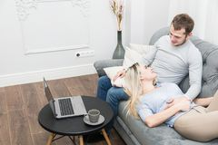 Young beautiful couple resting on the couch and watching online video from a laptop in the living room. stock images