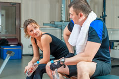 Young beautiful couple resting in a gym sitting Stock Images