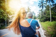 Young beautiful couple rides the jungle on a scooter, travel, fr. Eedom, happiness, vacation, honeymoon concept stock image