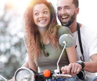 Attractive couple riding a scooter on a sunny day in the city Royalty Free Stock Image
